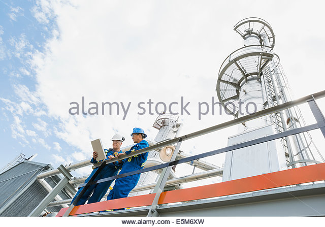 Male workers on platform at gas plant - Stock Image