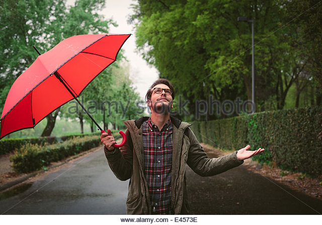Man checking if rain has stopped - Stock Image