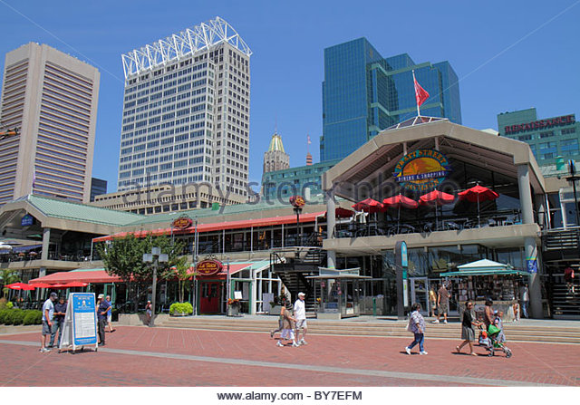 Baltimore Maryland Inner Harbor waterfront Harborplace festival marketplace attraction Black man woman pushing stroller - Stock Image