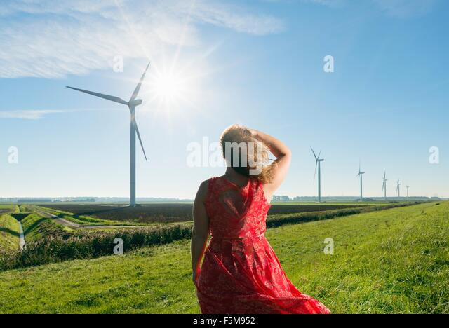 Mature woman standing in field, watching wind turbines on windfarm, rear view, Rilland, Zeeland, Netherlands - Stock Image