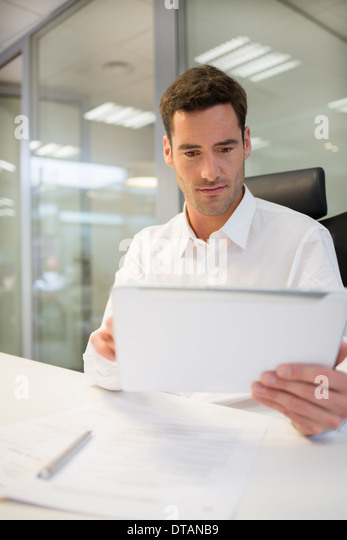 Businessman in office working on computer tablet - Stock Image