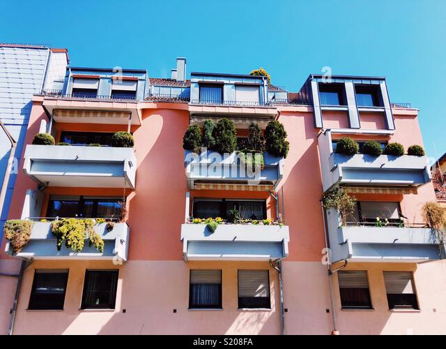 Spring in the city. Colored houses with pots of green on balcony - Stock Image