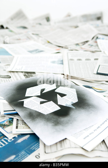 Recycling symbol stenciled on pile of newspapers - Stock Image