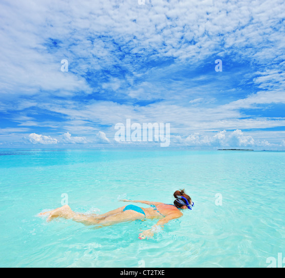 A woman with snorkeling mask diving in Kuredu resort, Maldives island, Lhaviyani atoll - Stock-Bilder