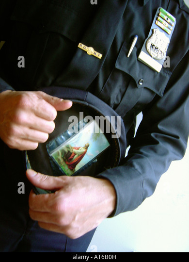 Artistic Portrait of a New York City Police Officer Holding His Hat Which Has a Prayer Card With An Image of Jesus - Stock Image