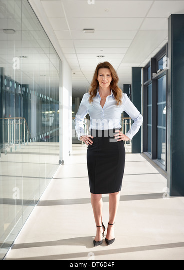Portrait of businesswoman in corridor - Stock Image