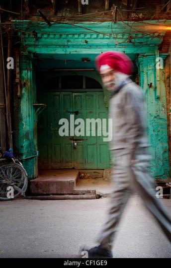 Red turbaned Indian Sikh  man before green door in the old city of Amritsar - Stock-Bilder