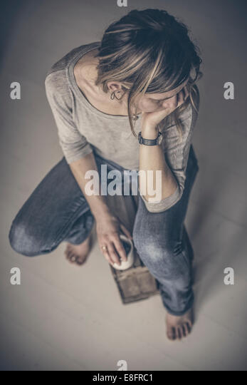 Overhead view of a thoughtful  woman sitting with cup of tea - Stock Image