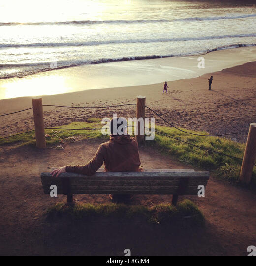 Man sitting on bench at sunset, Muir Beach, Marin, California, America, USA - Stock Image