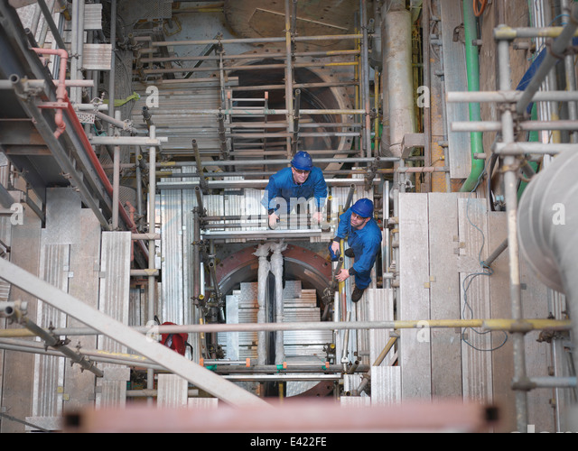 Portrait of engineers working deep down in equipment during power station outage, high angle view - Stock Image