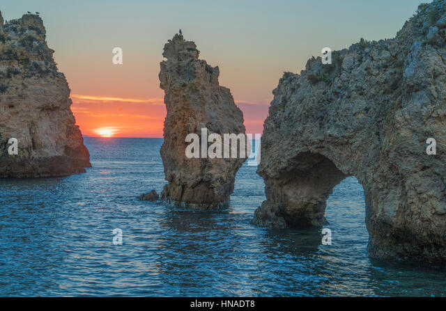 Sea arch at sunrise near Lagos, Portugal, Atlantic Ocean - Stock-Bilder