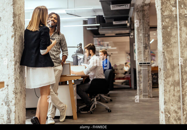 Business colleagues talking in the office  and smiling - Stock Image