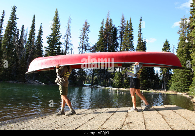 Couple walking to lake with a canoe over their heads - Stock-Bilder
