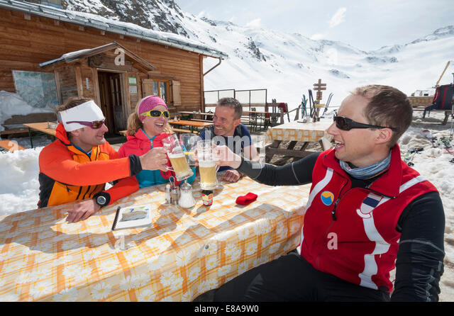 Group skiers cabin lunch beer winter snow - Stock Image