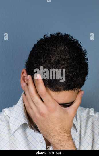 Young man hiding his face in shame - Stock Image