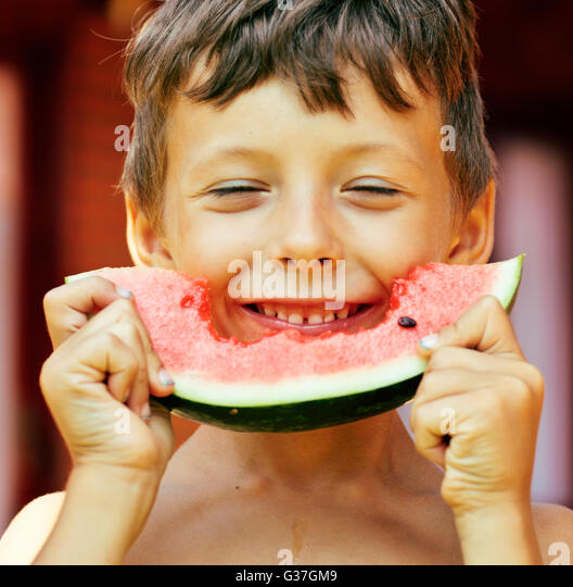 cute young little boy with watermelon crustes smiling - Stock Image