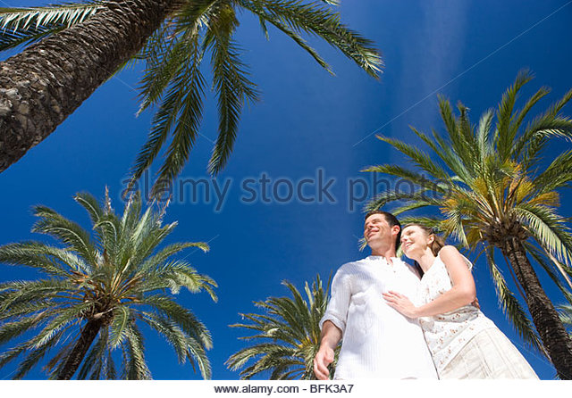 Smiling couple hugging under palm trees - Stock Image