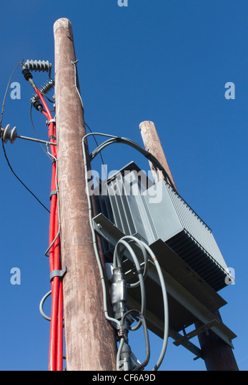 Mains electrical supply transformer on external supporting poles and transmission lines. - Stock Image