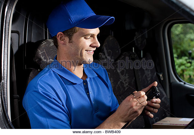 Delivery man in van with handheld computer - Stock Image
