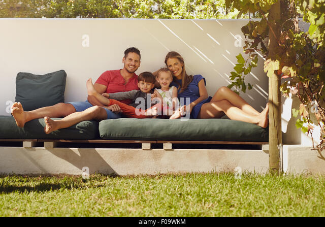 Portrait of happy young family sitting on patio smiling at camera. Couple with kids sitting on couch in their backyard. - Stock Image