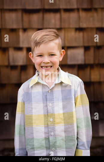 Young boy outdoors in a lifestyle portrait with natural light. - Stock Image