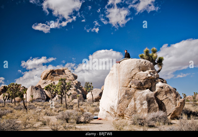 A young man sits on a lone bolder after climbing a route in Joshua Tree National Park. - Stock Image