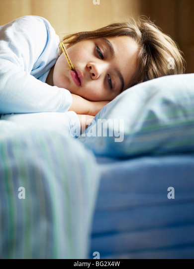 girl holding thermometer in bed - Stock Image