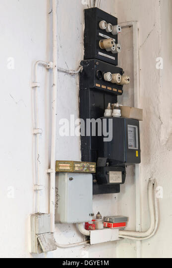 Old fuse box with an electricity meter and electrical wiring on a wall in a basement of an old building, Stuttgart - Stock Image