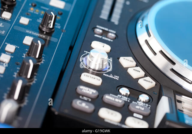 Closeup detail of a DJs music deck with turntable and control knobs for mixing, fading, equalizer and volume - Stock-Bilder