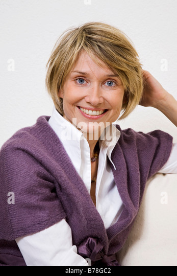 Woman sitting on a sofa - Stock Image