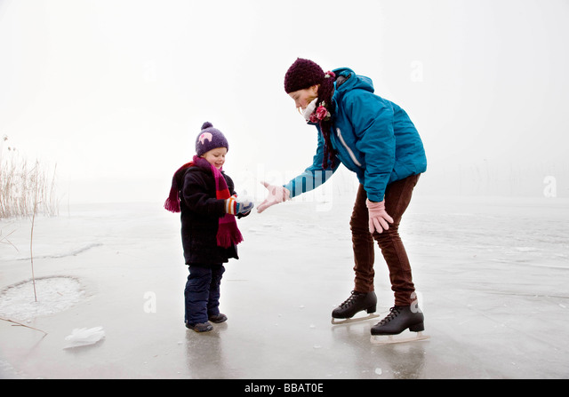 Girl and boy iceskating on frozen lake - Stock Image