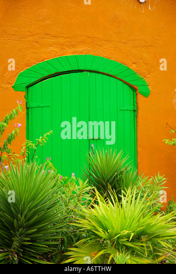 Bahamas colonial style door bright green color yellow wall - Stock Image