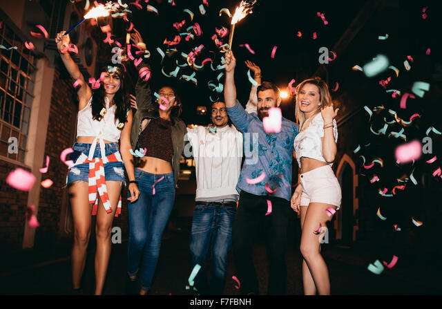 Group of young people having a party, outdoors. Multiracial young men and women celebrating with confetti. Best - Stock Image