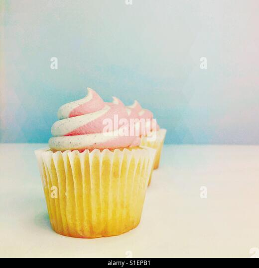 Vanilla cupcakes topped with strawberry and vanilla buttercream frosting. Square crop. Pastel colours. Space for - Stock-Bilder