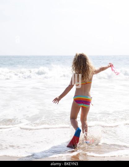 Girl splashing in waves - Stock Image