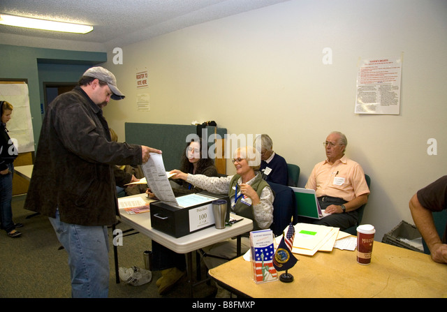 paper ballot into a ballot box at a polling station in Boise Idaho USA ...