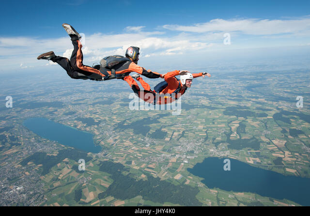 An skydiving instructor is taking a student on a training jump during an AFF course at Beromünster, Switzerland - Stock Image