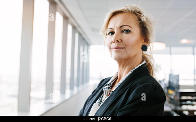 Portrait of mature businesswoman looking at camera confidently. Horizontal shot of beautiful caucasian female entrepreneur - Stock Image