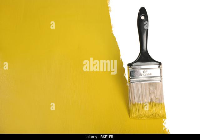 Brush painting wall with yellow paint - Stock-Bilder