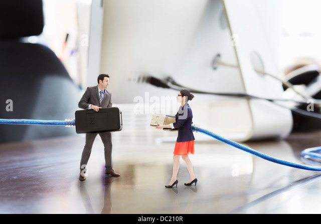 Office colleagues holding large computer cables on oversized desk - Stock Image