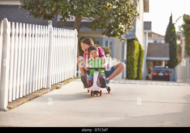 Siblings cycling on driveway - Stock Image