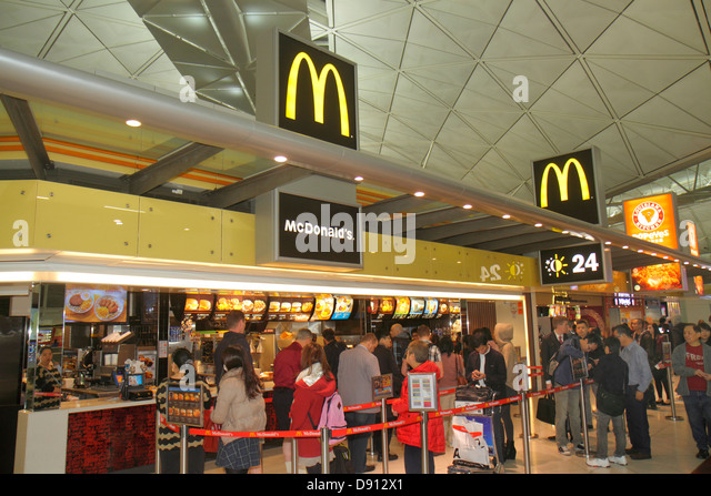 Hong Kong China International Airport HKG terminal concourse gate area inside interior food court Popeye's McDonald's - Stock Image