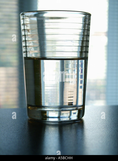 I'm positive the glass is half full, half empty - Stock Image