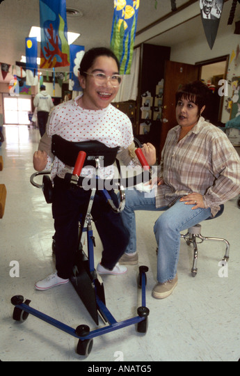 New Jersey East Orange Cerebral Palsy Center disabled student female therapist Hispanic girl walker - Stock Image