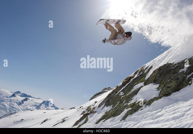 Snowboarder jumping over a cliff in the ski resort of Disentis 3000 - Stock Image