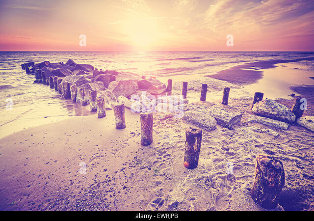 Retro vintage style beautiful sunset over Baltic Sea coast with lens flare effect, Miedzyzdroje in Poland. - Stock Image
