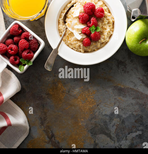 Steel cut oatmeal porridge with raspberry and coconut flakes for breakfast overhead shot whith copyspace - Stock Image