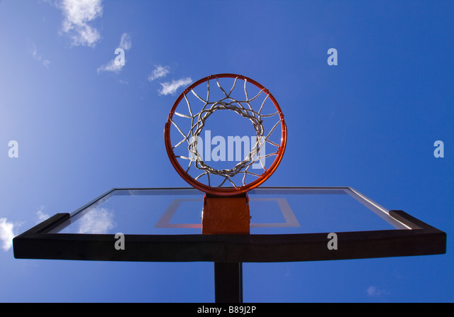 Basketball hoop net and backboard directly overhead with clouds and blue sky - Stock Image