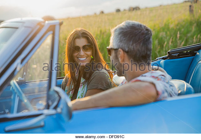 Happy couple on road trip in convertible - Stock Image