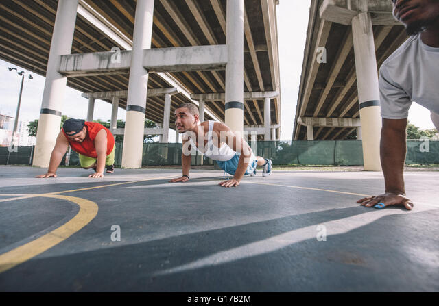 Low angle view of friends on basketball court doing push ups - Stock Image